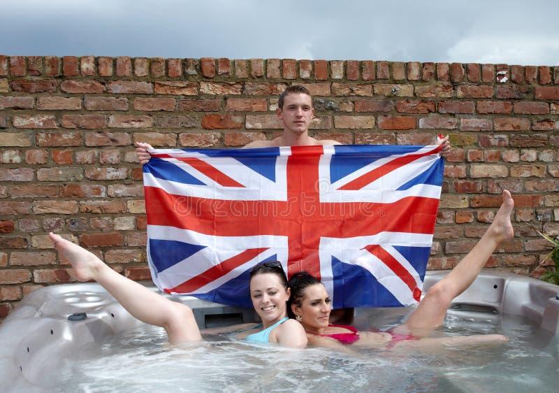 Drie mensen met Union Jack in een Jacuzzi stock fotografie