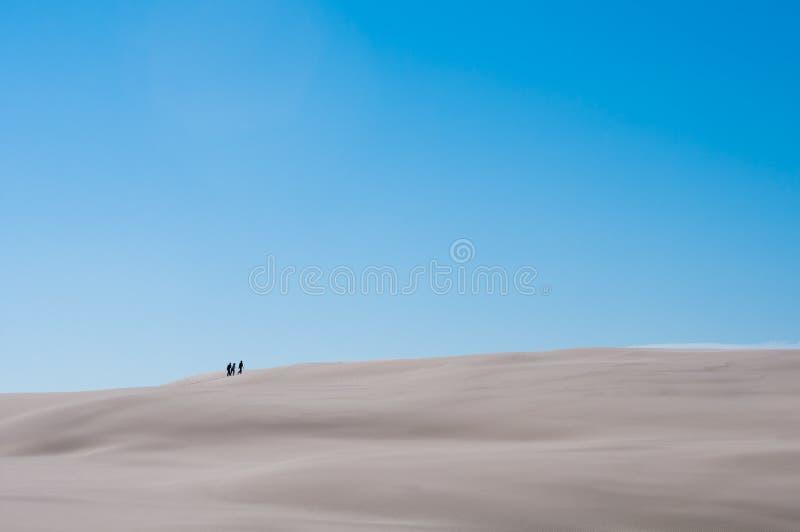 Drie Mensen op Sandy Dune With Blue Sky-Achtergrond royalty-vrije stock afbeelding