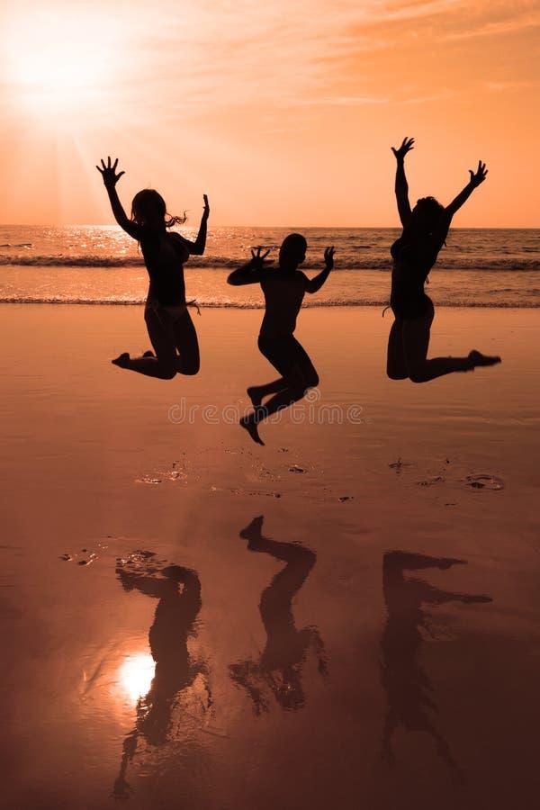 Drie mensensilhouetten die op het strand springen stock afbeeldingen