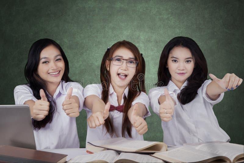 Drie middelbare schoolstudenten het tonen beduimelt omhoog stock fotografie