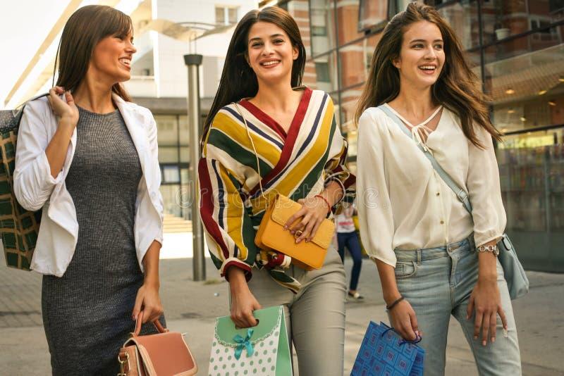 Drie modieuze jonge vrouwen die met het winkelen zakken wandelen stock afbeeldingen