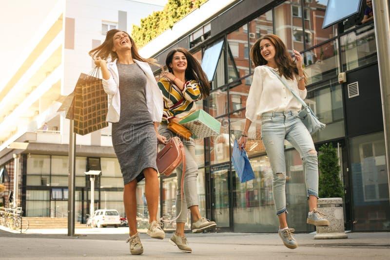Drie modieuze jonge vrouwen die met het winkelen zakken wandelen Sati royalty-vrije stock fotografie