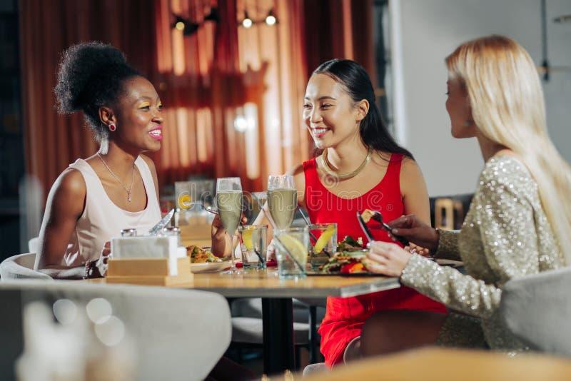 Drie modieuze vrouwen die modieuze kleding dragen die diner hebben stock afbeelding