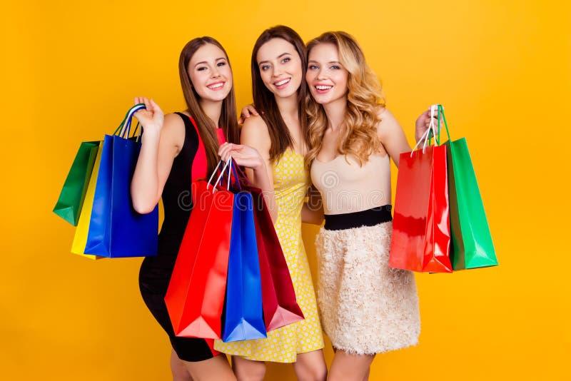 Drie mooie, charmante, succesvolle meisjes die in kleding colo houden royalty-vrije stock fotografie