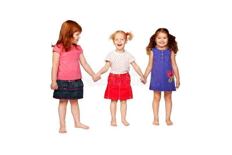 Drie mooie glimlachende meisjes die handen houden stock afbeeldingen