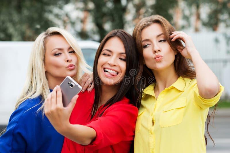 Drie mooie jonge en vrouwen die stellen grimassen trekken stock fotografie