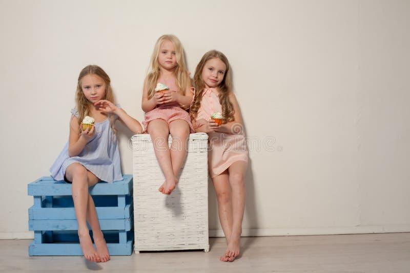 Drie mooie jonge meisjes en zoete suikergoedlollys stock afbeeldingen
