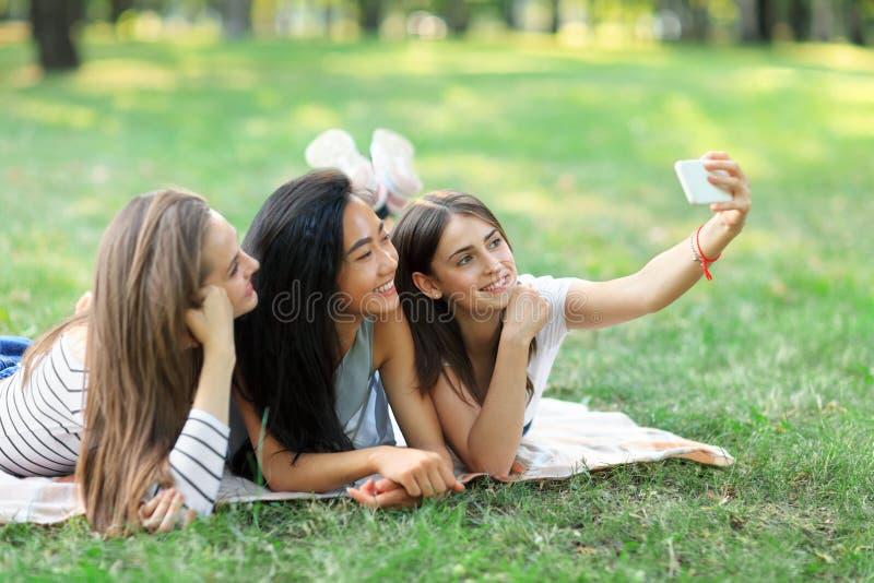Drie mooie jonge op gras liggen en vrouwen die selfies nemen stock foto's