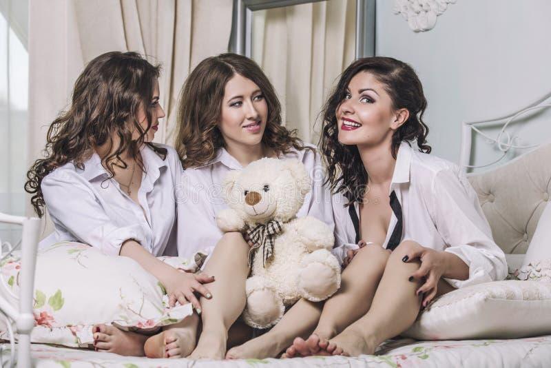 Drie mooie jonge vrouwenvrienden die in de slaapkamer binnen babbelen royalty-vrije stock foto's