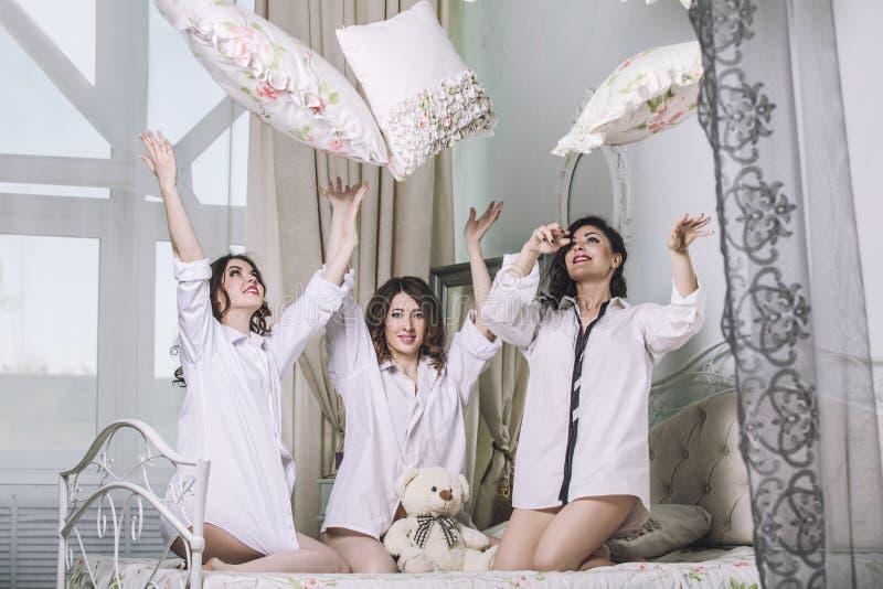 Drie mooie jonge vrouwenvrienden die in de slaapkamer binnen babbelen royalty-vrije stock foto