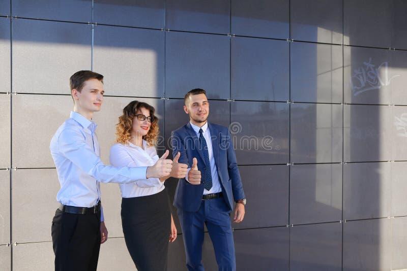 Drie mooie jongeren die duimen tonen, het lachen, smilin stock foto's