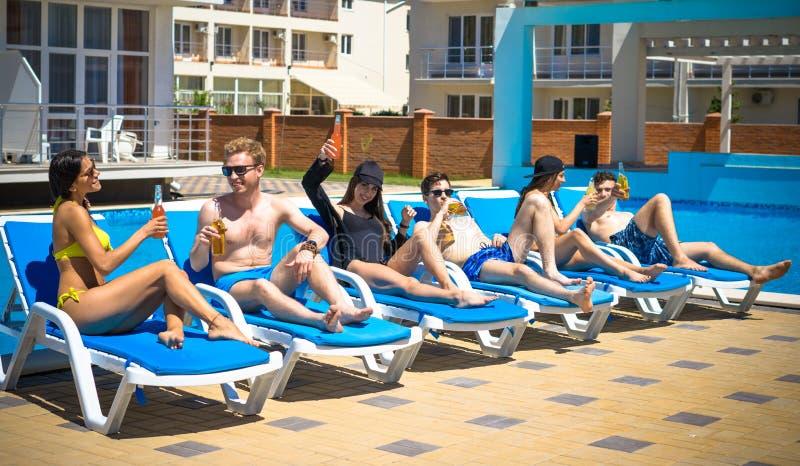 Drie Mooie meisjes die cocktails drinken dichtbij de pool royalty-vrije stock foto's
