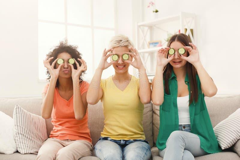 Drie mooie meisjes die ogen behandelen met komkommerstukken stock foto's