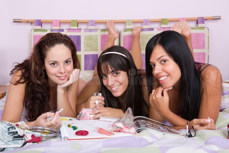 Drie mooie meisjes die samen van op het bed genieten royalty-vrije stock foto's