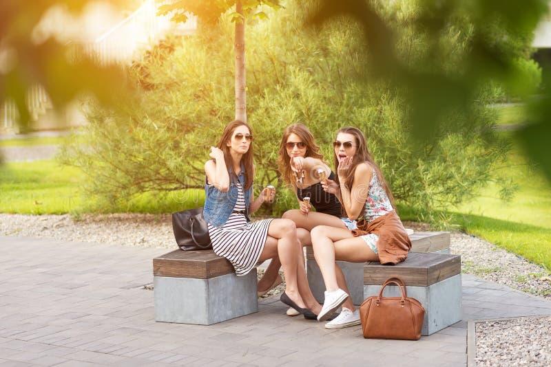 Drie mooie meisjes eten roomijs, die onder de boom stellen royalty-vrije stock afbeelding