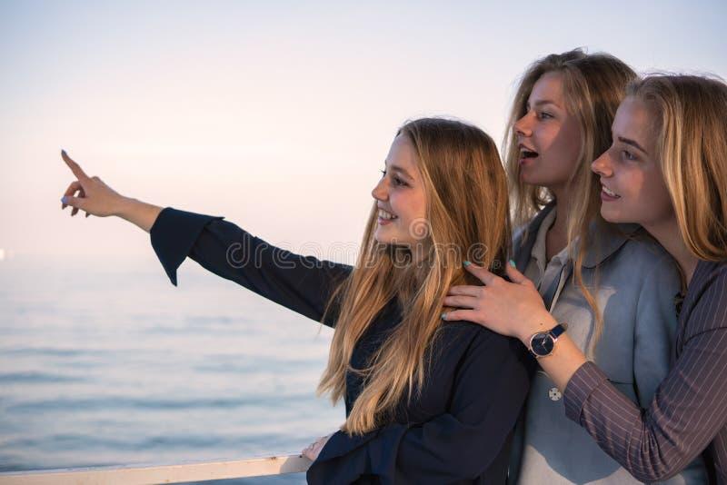 Drie Mooie tienervriendenmeisjes die pret hebben dichtbij het overzees het richten ergens ver weg met een vinger royalty-vrije stock afbeeldingen