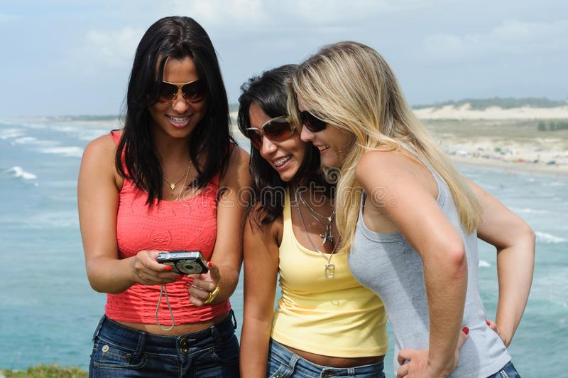 Drie mooie vrouwen die selfie op het strand nemen stock afbeeldingen