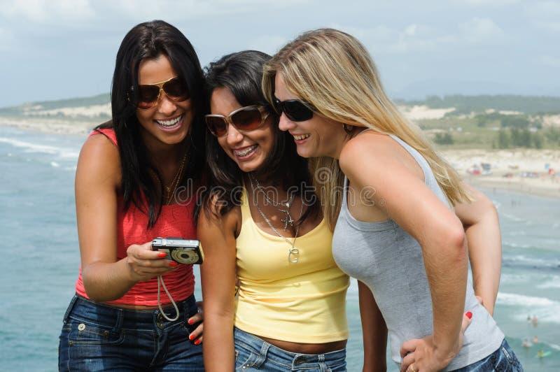 Drie mooie vrouwen die selfie op het strand nemen stock afbeelding