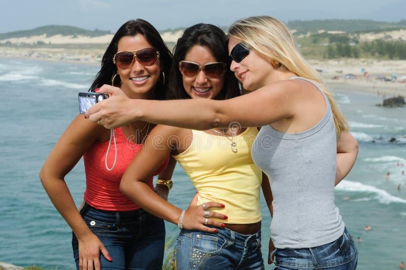 Drie mooie vrouwen die selfie op het strand nemen stock foto's