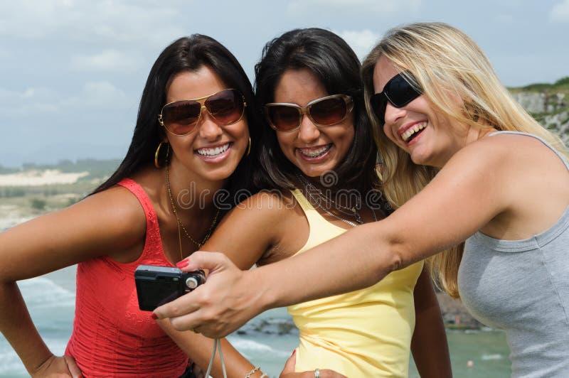 Drie mooie vrouwen die selfie op het strand nemen royalty-vrije stock fotografie
