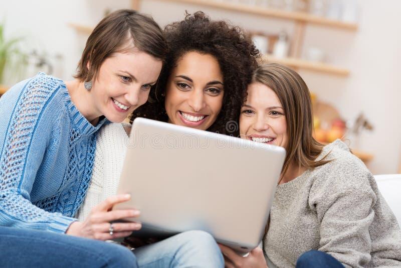 Drie mooie vrouwen met een laptop computer royalty-vrije stock afbeelding
