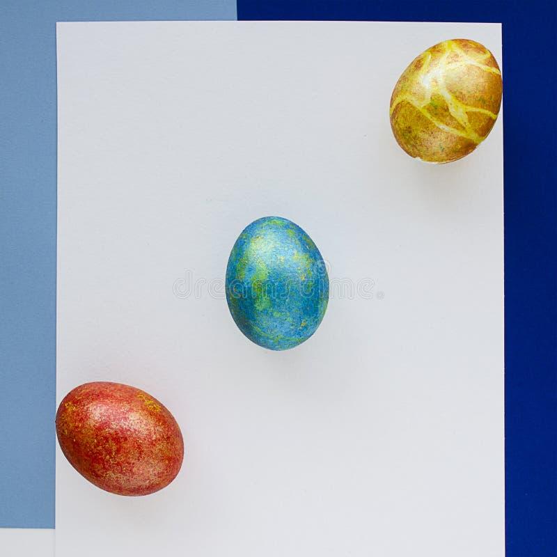 Drie multi-colored eieren Gelukkige Pasen Blauwe document achtergrond royalty-vrije stock afbeeldingen