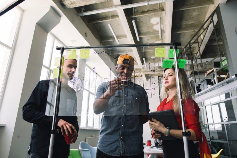 Drie multiethnical zakenlui die in vrijetijdskleding en planningsconcept, die in zolderbureau samenwerken bespreken met royalty-vrije stock afbeeldingen