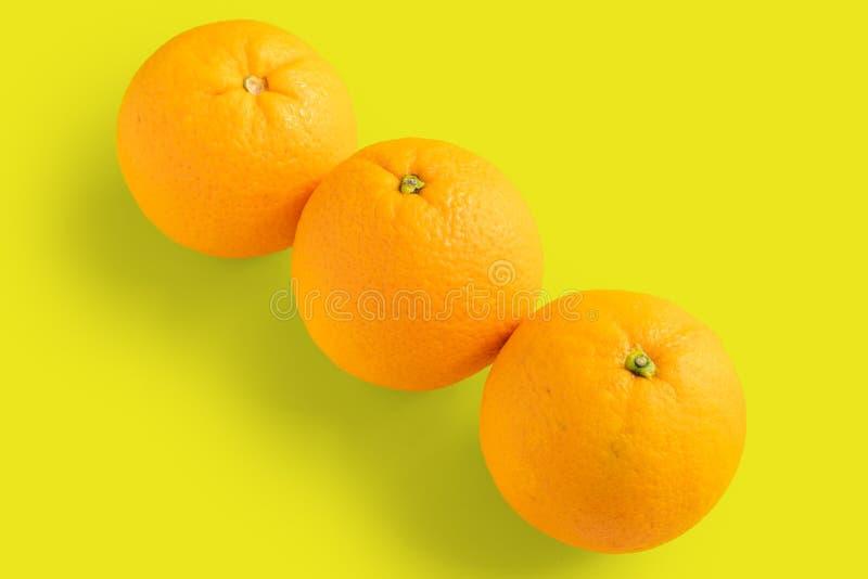 Drie navelsinaasappelen op gele achtergrond royalty-vrije stock fotografie