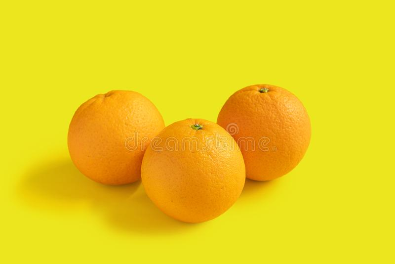 Drie navelsinaasappelen op gele achtergrond royalty-vrije stock foto's