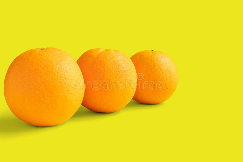Drie navelsinaasappelen op gele achtergrond stock afbeeldingen