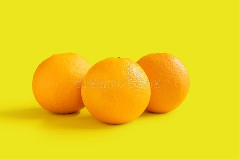 Drie navelsinaasappelen op gele achtergrond royalty-vrije stock afbeeldingen