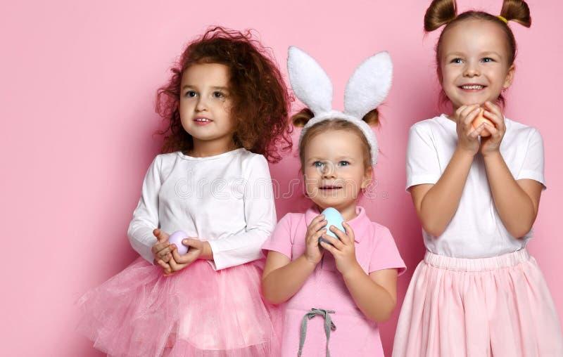 Drie omhoog gekleed voor de meisjes van het vakantiejonge geitje met geschilderde eieren wachten op een mirakel op Pasen-dag stock foto's