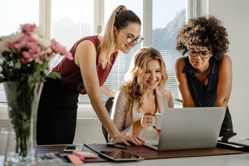 Drie onderneemsters die laptop en het glimlachen bekijken stock fotografie