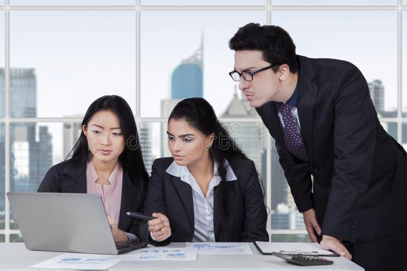 Drie ondernemers die een baan in bureau plannen stock fotografie