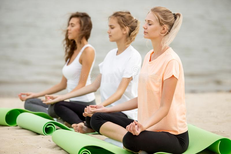 Drie ontspannen jonge meisjes zitten in de lotusbloemposities met het sluiten van ogen die yoga op matten op zandig strand op een royalty-vrije stock afbeelding