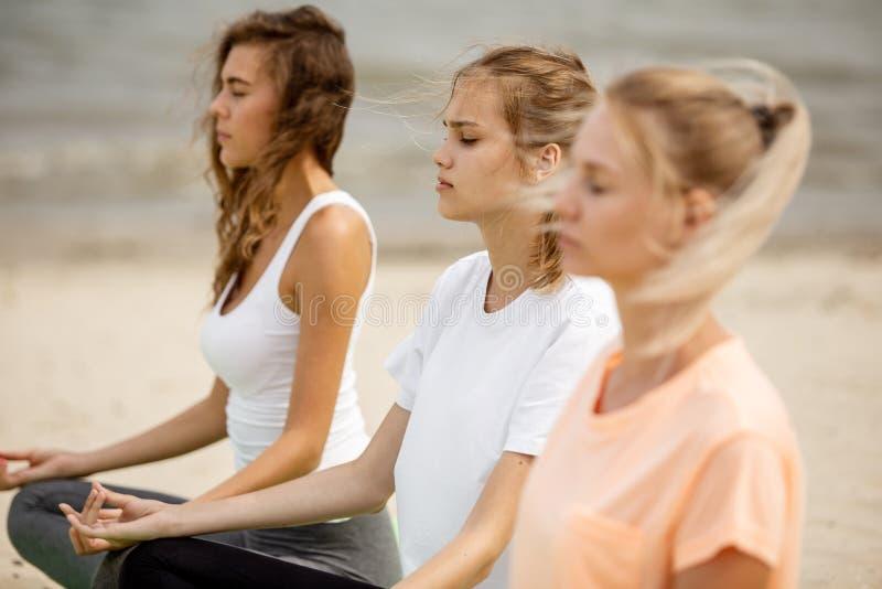 Drie ontspannen jonge meisjes zitten in de lotusbloemposities met het sluiten van ogen die yoga op matten op zandig strand op een royalty-vrije stock foto's