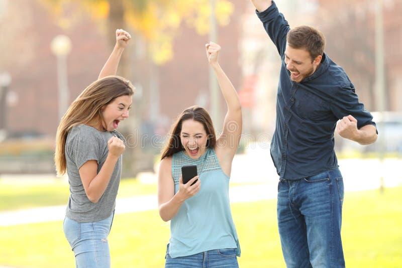 Drie opgewekte vrienden die controlerend smartphone in een park springen royalty-vrije stock afbeeldingen