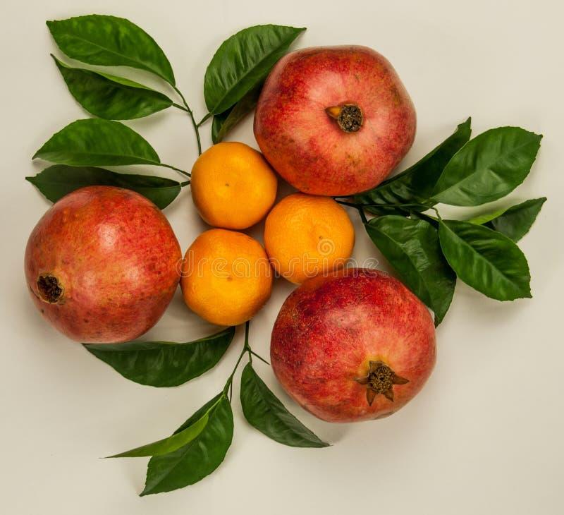 Drie oranje mandarins met drie rode granaatappels stock fotografie