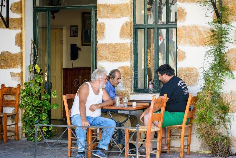 Drie oude mensen die bij Grieks taverna en het spelen backgammon zitten royalty-vrije stock afbeelding
