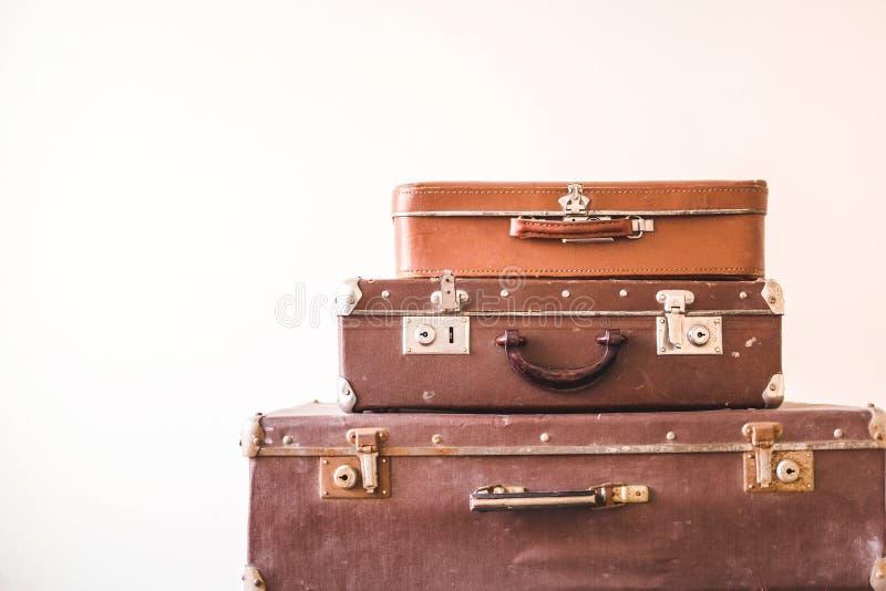 Drie oude uitstekende koffers tegen een lichte muurachtergrond Rustieke retro stijl stock fotografie