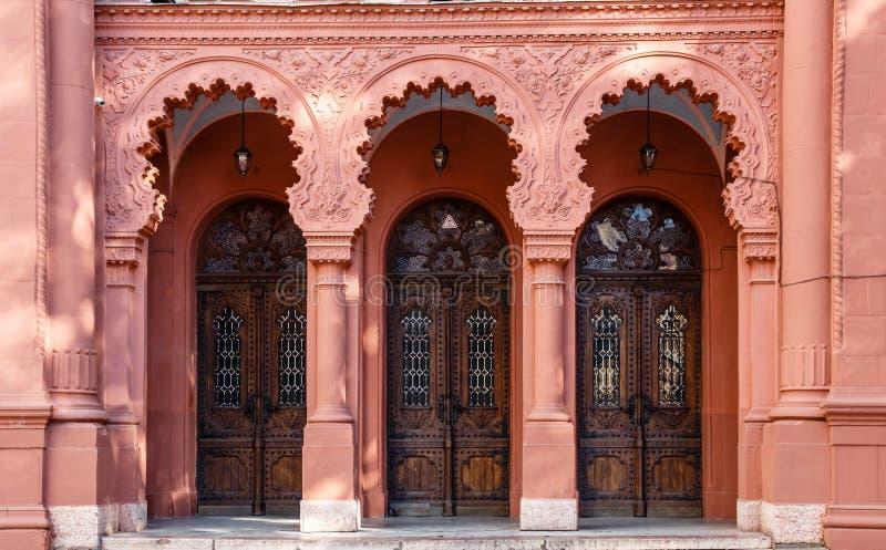 Drie overspanden op een rij houten deuren op de rode voorgevel van Synagoge van Uzhgorod, de Oekraïne royalty-vrije stock fotografie