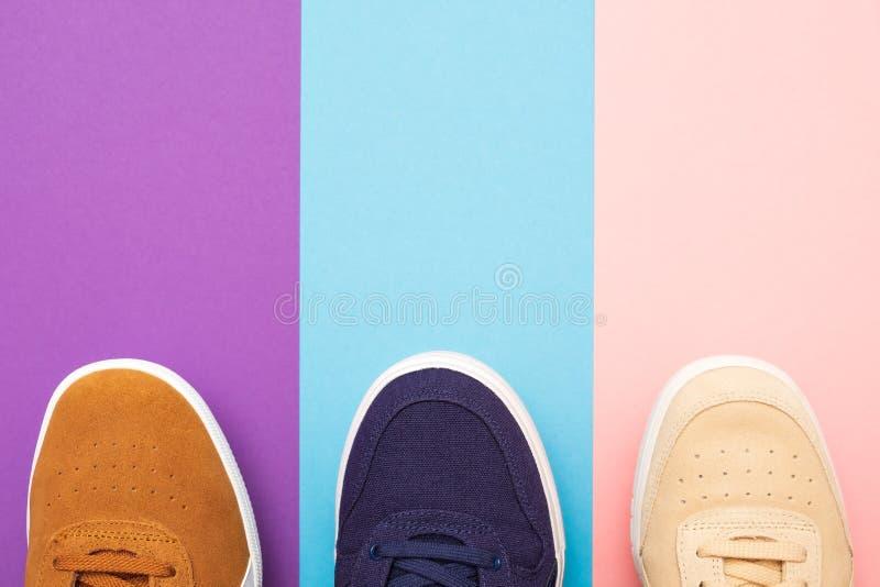 Drie paar tennisschoenen op gekleurde achtergrond stock foto's
