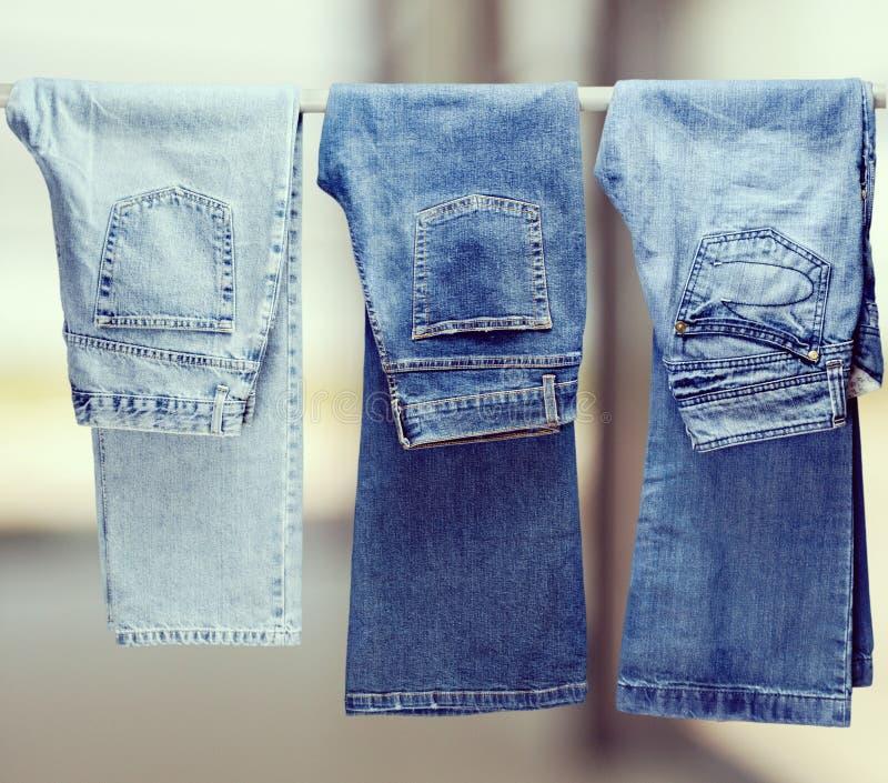 Drie paar verschillende jeans die op spoor hangen royalty-vrije stock afbeelding