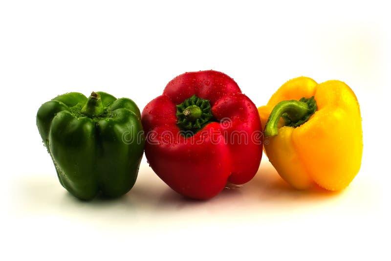 Drie paprika's in een lijn op wit stock afbeelding