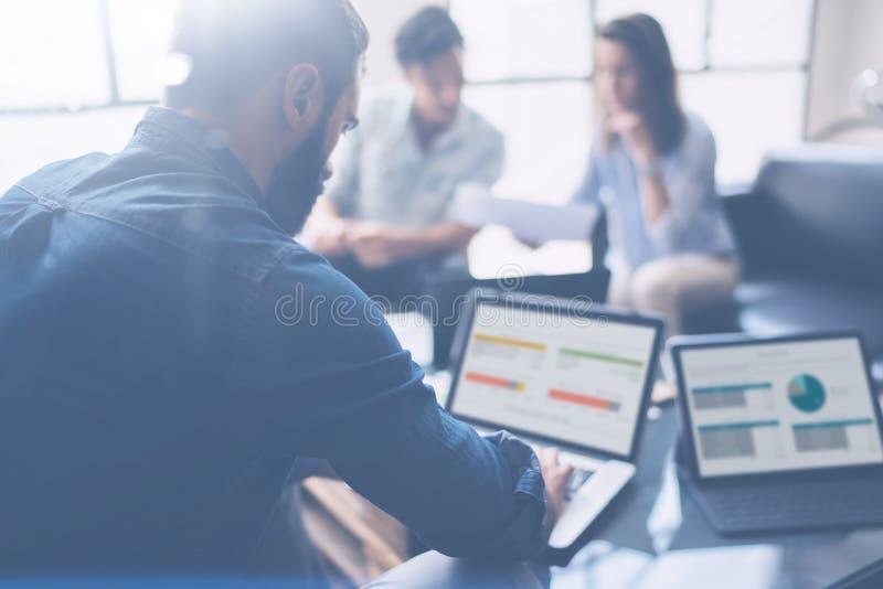 Drie partners die onderzoek voor nieuwe bedrijfsrichting maken Jonge zakenman die moderne laptop werken en documenten tonen royalty-vrije stock afbeeldingen