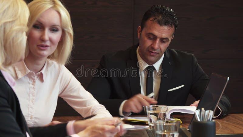 Drie partners kwamen in het bureau voor een commerciële vergadering samen stock foto