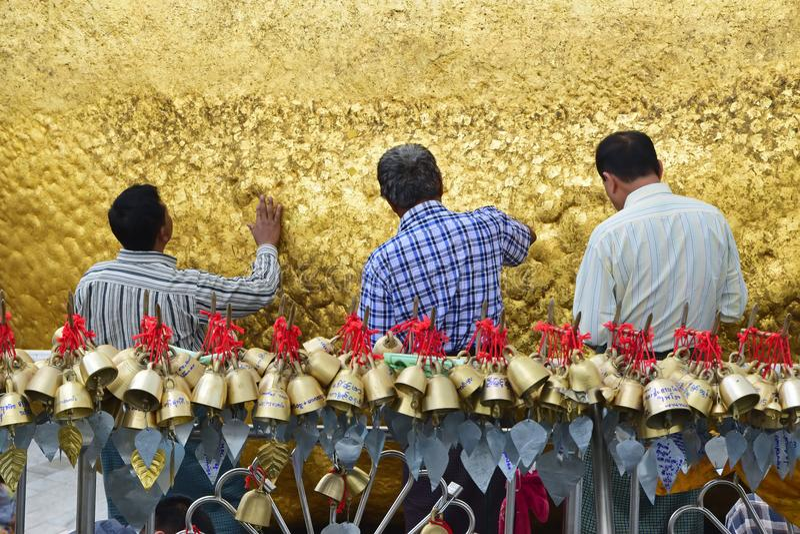 Drie Pelgrims die gouden foliesbladeren samen op gouden rots kleven bij de Kyaiktiyo-Pagode met kleine klokken in voorgrond stock fotografie