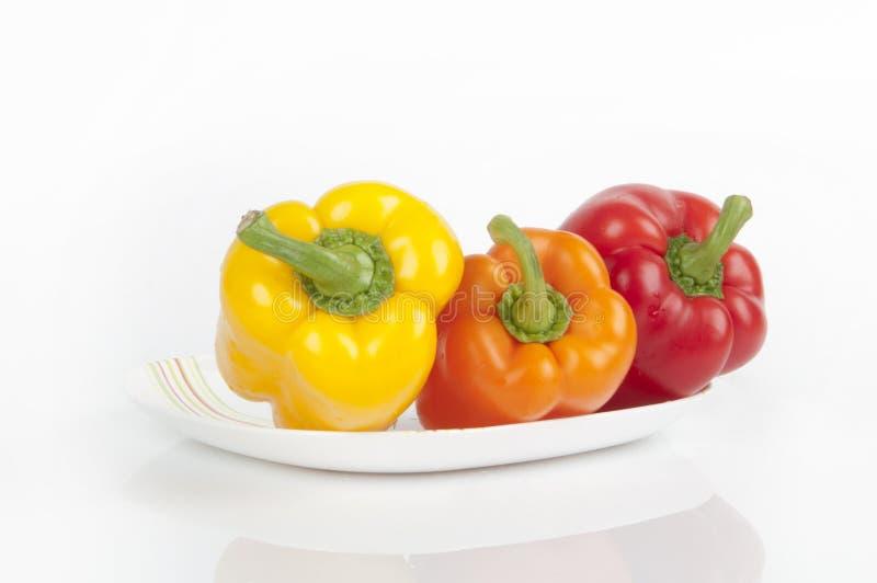 Drie peper op een plaat stock afbeeldingen