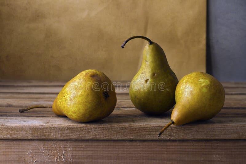 Drie peren op houten lijst stock afbeeldingen