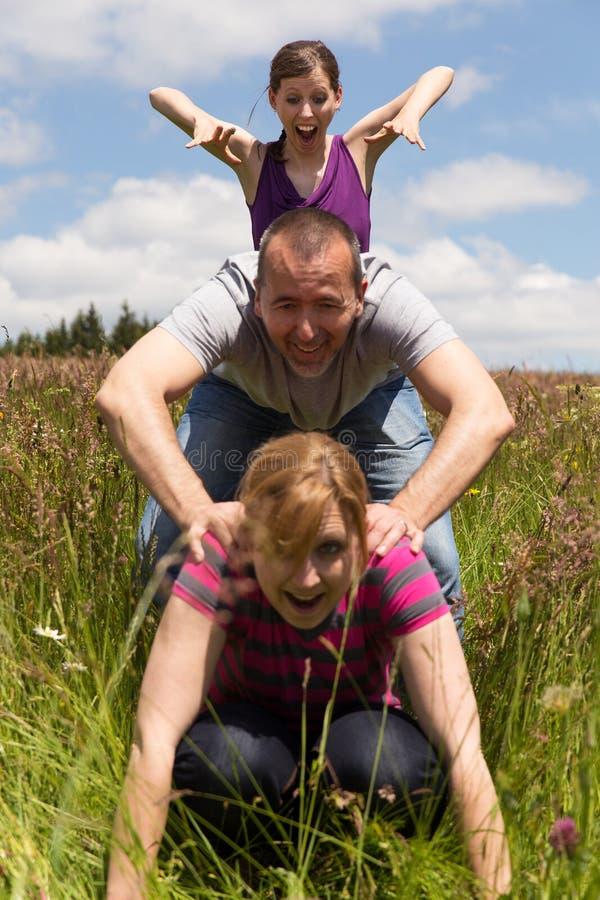 Drie personen maken een leapfrog sprong stock fotografie
